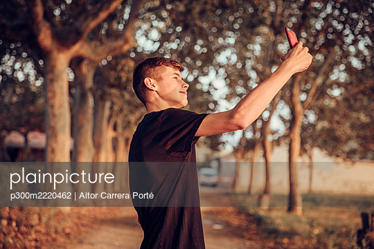 Teenage boy taking selfie while standing on road - p300m2220462 by Aitor Carrera Porté