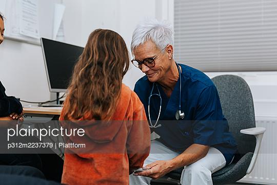 Doctor examining girl in office - p312m2237379 by Plattform