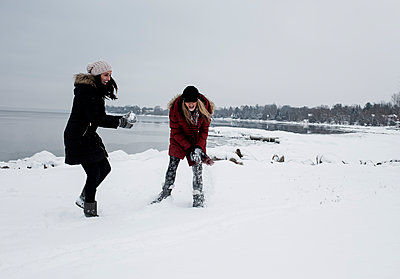 Female friends playing with snow at beach against sky during winter - p1166m1553421 by Cavan Images