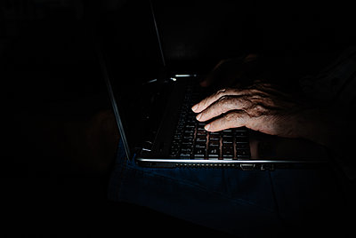 Anonymous aged person using laptop in darkness - p1166m2218541 by Cavan Images