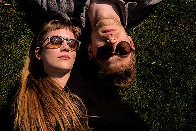 Junges Paar sonnt sich auf der Wiese - p1212m1138842 von harry + lidy