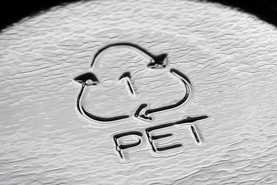 PET recycling symbol on the bottom of a plastic food packaging container - p1302m1590096 by Richard Nixon