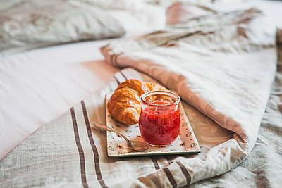 Plate with croissant and glass of strawberry jam on bed - p300m1153626 by Anke Scheibe