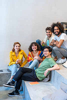 Portrait of group of friends sitting on stairs having a drink - p300m2113858 by VITTA GALLERY