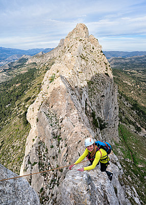 Smiling woman mountaineering at Bernia Ridge, Costa Blanca,  Alicante, Spain - p300m2169899 by Alun Richardson