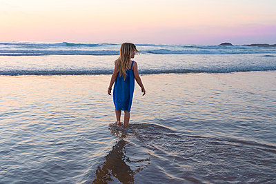 Girl in blue dress looking at view while walking at beach during sunset - p300m2244078 by Steve Brookland