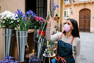 Young female florist holding flower while working at shop during COVID-19 - p300m2274929 by Ezequiel Giménez
