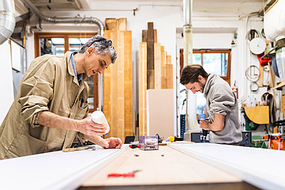 Mature male owner and colleague working on table at workshop - p300m2293663 by Eugenio Marongiu