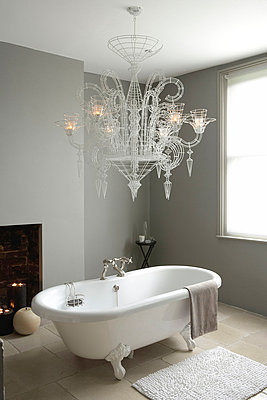Roll top bath and oversized Neo-Baroque chandelier lit with candles in grey painted bathroom with stone floor tiles - p3493212 by Jon Day