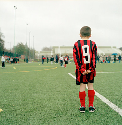 boy in football gear standing on pitch - p3880272 by Ulrike Leyens