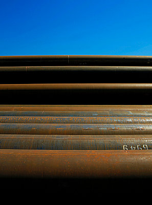 Rusted pipes piled against blue sky - p42916990 by Charlie Fawell