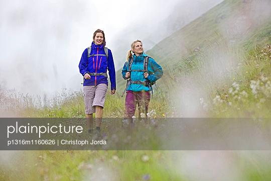 Zwei Wanderinnen gehen über eine Wiese, Alpe-Adria-Trail, Nockberge, Kärnten, Österreich - p1316m1160626 von Christoph Jorda