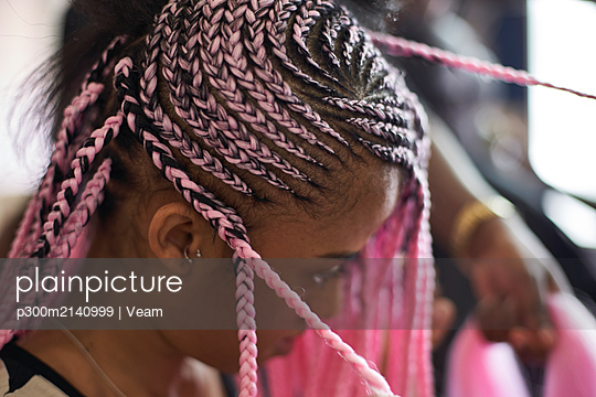 Young woman with pink braids, close-up - p300m2140999 by Veam