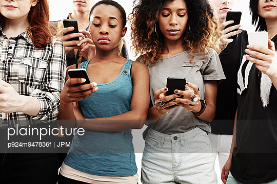 Studio shot of six young adults texting on smartphone - p924m947836f by JPM