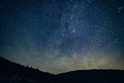 Scenic view of silhouette landscape against star field at night - p1166m1226154 by Cavan Images