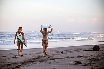 Indonesia, Bali, two women carrying surfboards on the beach - p300m1023553f by Konstantin Trubavin