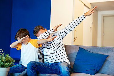 Father and son making a dab on couch at home - p300m1562209 by Bonninstudio