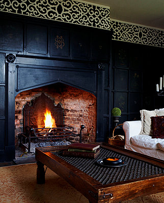Open fire in living room of black panelled Georgian farmhouse  - p349m789832 by Brent Darby