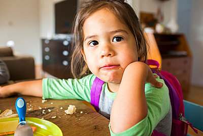 Messy mixed race girl eating food and wearing backpack at table - p555m1504329 by Adam Hester