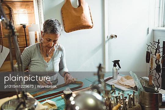 Attentive craftswoman cutting leather - p1315m1229673 by Wavebreak