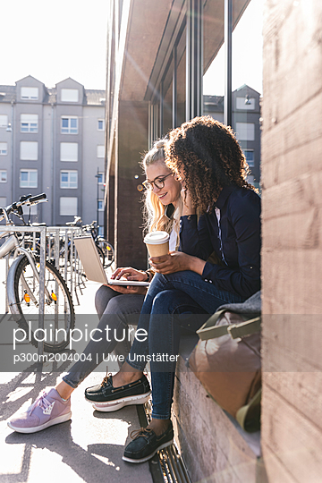 Friends sitting in front of window in the city, using laptop - p300m2004004 von Uwe Umstätter