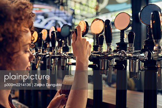 Female barkeeper tapping beer in a pub - p300m2214136 by Zeljko Dangubic