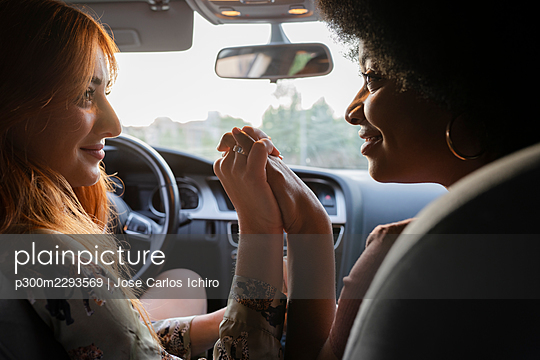 Smiling female friends looking at each other while holding hands in car - p300m2293569 by Jose Carlos Ichiro