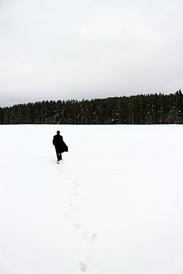 Person walking in snow - p1019m2141947 by Stephen Carroll