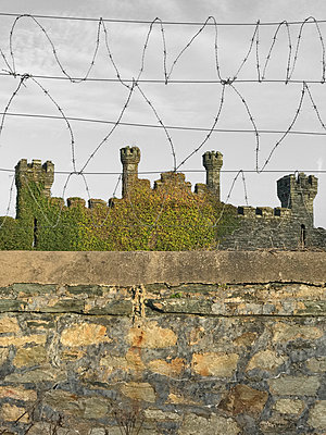 Folly castle with barbed wire fence - p1048m2016693 by Mark Wagner