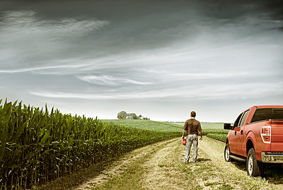 Rear view of farmer standing by car on field against cloudy sky - p1166m1211379 by Cavan Images