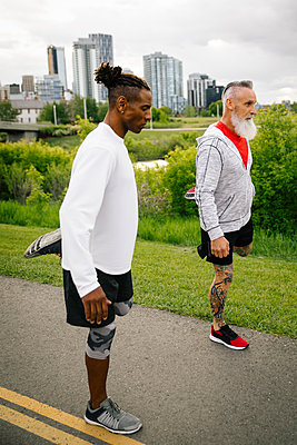 Mature male runners stretching legs on urban park path - p1192m2109972 by Hero Images