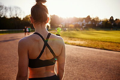Rear View Of Woman Standing By Outdoor Running Track - p1407m1508962 by Monkey_Images