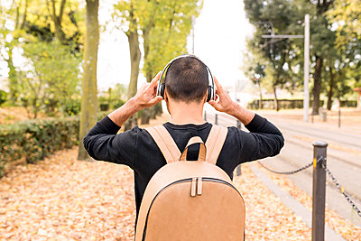 Young man with headphones and backpack outdoors - p300m1535120 by Francesco Morandini