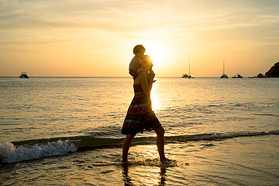 Thailand, Koh Lanta, silhouette of mother with baby girl on her shoulders at seashore during sunset - p300m2070343 von Gemma Ferrando