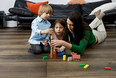 A mother and her children playing with building blocks - p30118474f by Paul Hudson