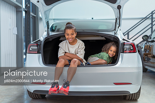 UK, Portrait of sister (2-3) and brother (8-9) sitting in car trunk in showroom - p924m2300844 by Monty Rakusen