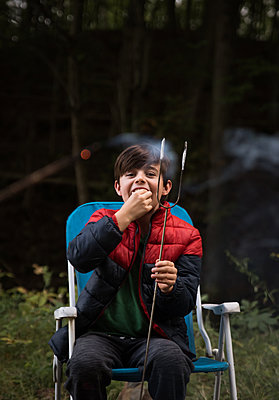 Young boy eating a marshmallow off of a metal stick outdoors. - p1166m2214644 by Cavan Images