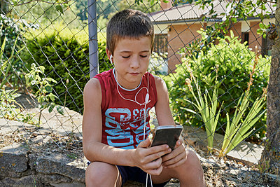 Boy looking at their smart phones and listening to music with headphones sitting on a stone wall in sunny day. Technology concept - p1166m2235253 by Cavan Images