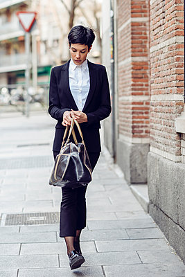 Portrait of young businesswoman  with bag walking on pavement - p300m1568117 by Javier Sánchez Mingorance