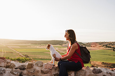 Smiling woman holding dog while sitting on rock against sky - p300m2251336 by Eva Blanco