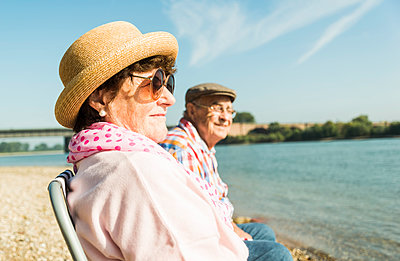 Germany, Ludwigshafen, senior couple sitting on folding chairs at riverside - p300m1068911f by Uwe Umstätter