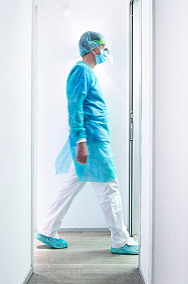 Mature male dentist walking in illuminated hallway at clinic - p300m2198390 by Jose Luis CARRASCOSA
