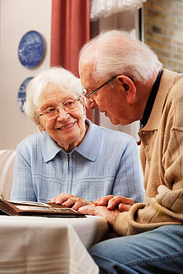 Senior couple watching old photographs at home - p300m884967f by Ingo Bartussek