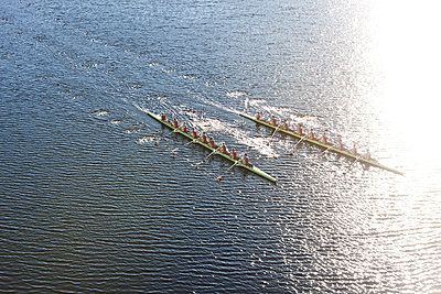 Elevated view of two rowing eights in water - p300m975562f by zerocreatives