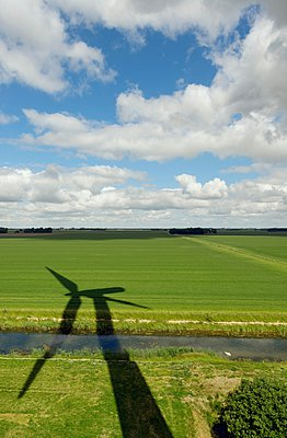 Shadow of a wind turbine on the meadow - p429m1047210 by Mischa Keijser