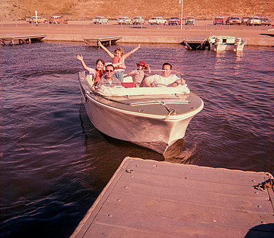 Portrait of smiling Caucasian family waving on boat near dock - p555m1444192 by PBNJ Productions