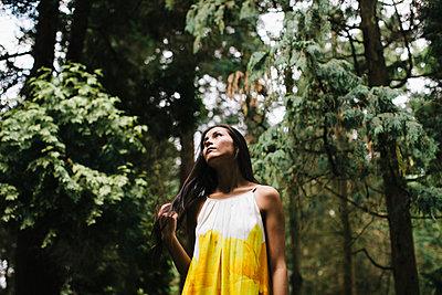 Junge Frau im gelben Kleid steht im Wald - p586m953783 von Kniel Synnatzschke