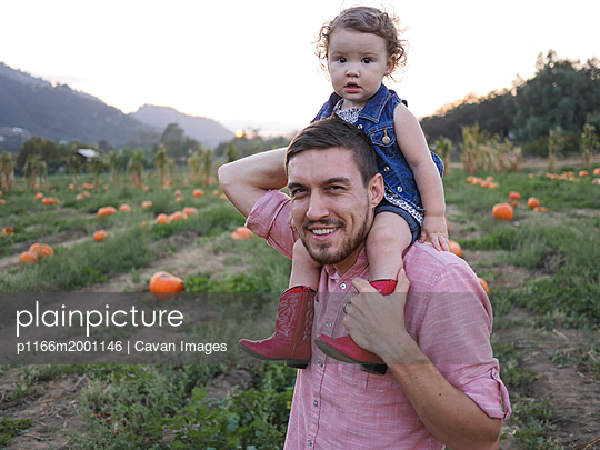 Portrait of father carrying daughter on shoulders while standing at pumpkin patch against clear sky - p1166m2001146 by Cavan Images