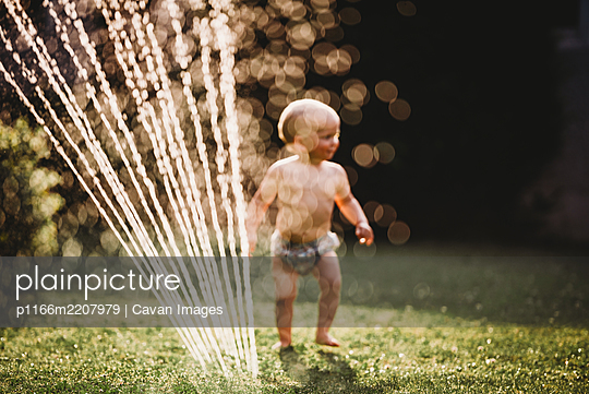 Bokeh baby in garden playing with water from sprinkler - p1166m2207979 by Cavan Images