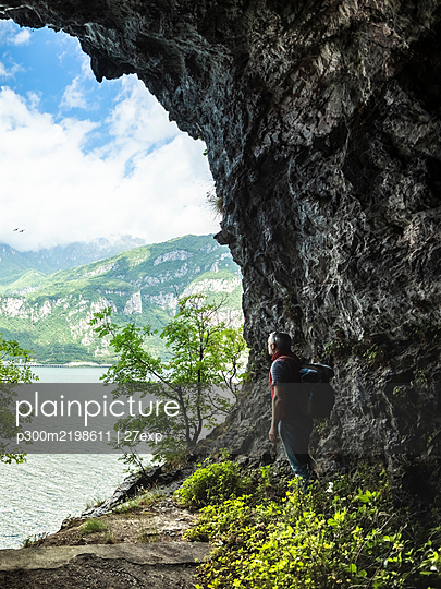 Mature man with backpack standing by rock formation while looking at Lake Como from cave entrance - p300m2198611 by 27exp